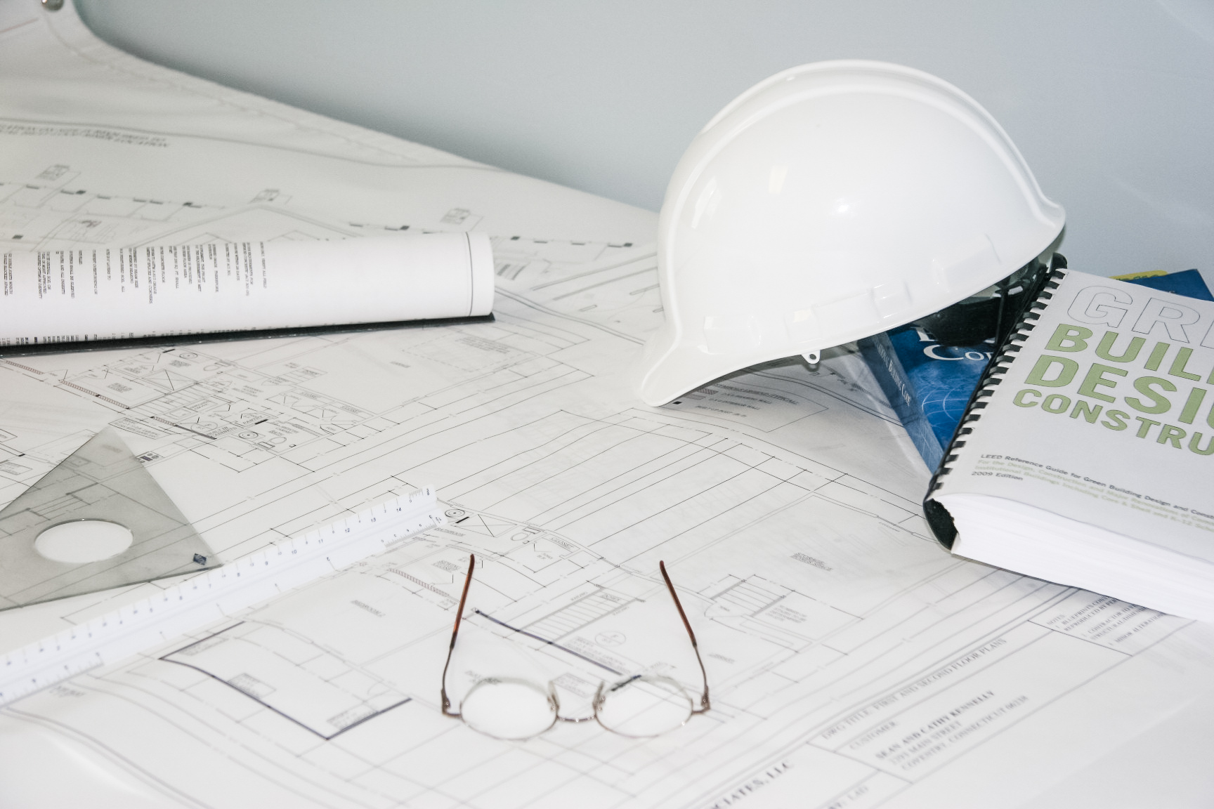 Consulting engineering plans beneaht a hard hat and other tools of the trade